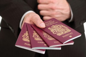 Businessman presenting four British passports at customs or check in area